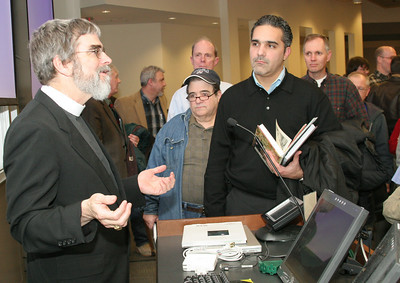 Mariano Maluf of St. Michael the Archangel Church, Woodstock, holding the books, listens as Jesuit Brother Guy Consolmagno, continues a discussion with a small group of people following his talk at Emory University's Candler School of Theology.