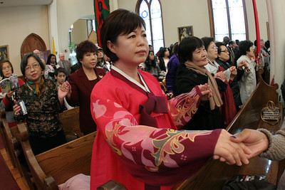Lucia Hong of the Korean Martyrs Church, Doraville, joins hands with others during the praying of the Our Father.