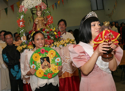 Wearing a princess dress made by the Filipino community, Magnerica Malley leads a procession around the gymnasium at the conclusion of the Mass.
