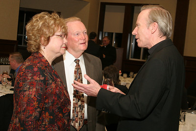 Theresa and Jim Smith of St. Joseph Church, Marietta, speak with Father Neil Herlihy, pastor of St. Peter the Rock Church, The Rock, during the pre-dinner Shepherd's Night reception.