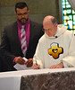 Fr. Steve finalizes the paperwork — at Sacred Heart School of Theology.