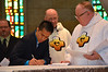 James signs the documents of his first vows — at Sacred Heart School of Theology.