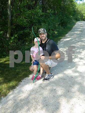Brian Whitmore teaching Ellasyn Whitmore how to shoot a bow and arrow.