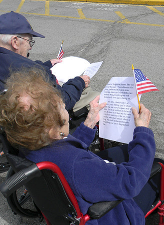 A Southpoint resident holds her flag as she joins in the singing of 'You're A Grand Old Flag.'  — Dan Irwin