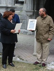 City Councilor Diosdado Lopez presents a plaque to Maria Mercedes, from La Familia Hispana, Inc..