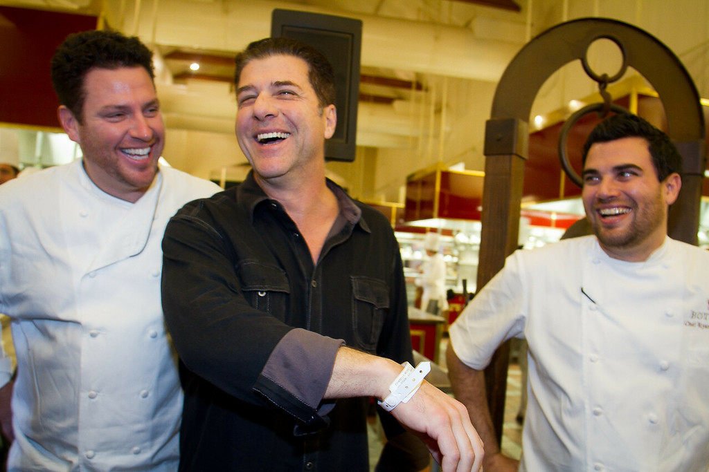 Michael Chiarello shows his hospital wrist band after just being released from the hospital for an appendectomy at the Napa Flavor event being held at the CIA Greystone  in St. Helena, Calif.,  on Saturday, November 19th, 2011. He is flanked by chefs Ryan McIllwraith, right, and Scott Conant