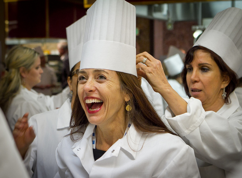 Valerie Kiadeh gets a chefs hat during the interactive lunch with Michael Chirarello during the Napa Flavor event being held at the CIA Greystone  in St. Helena, Calif.,  on Saturday, November 19th, 2011.