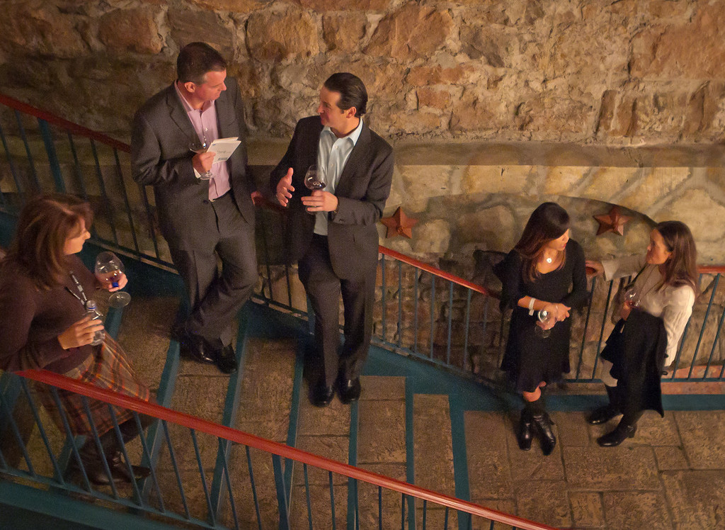 People enjoy some wine on the stairs at the Napa Flavor Gala being held at the CIA Greystone in St. Helena, Calif., on November 18th, 2011.