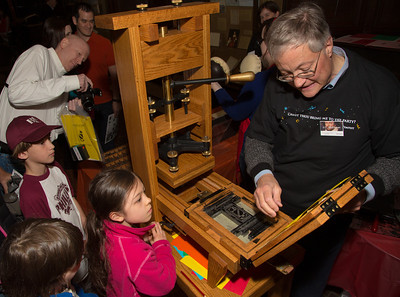 Twins  Ajanta and Etienne from Reston VA.(8 years old) get a demonstration of a real printing press from docent J.C. McElveen