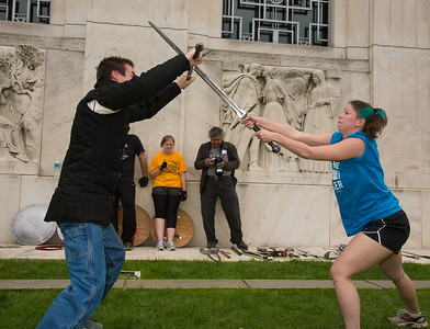 "Casey Kaleba demonstrates swordplay on Folger's front lawn. Kaleba's title is 'Fight Director""."