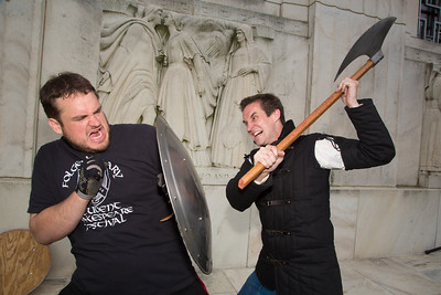 "Lex Davis (left) and Casey Kaleba demonstrate swordplay on Folger's front lawn. Kaleba's title is 'Fight Director""."