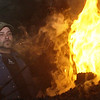 Record-Eagle/Garret Leiva<br /> Kent Cummings, of Ontario, Canada, stokes the fire as he brings a brick forge up to temperature Saturday at the Folly at the Forge held at Black Rock Forge in Traverse City.