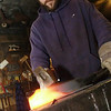 Record-Eagle/Garret Leiva<br /> Jason Kashazta, of Lake Ann, takes a hammer to his first blacksmith project - an ergonomic handle for his Kegerator, Saturday at the Folly at the Forge held at Black Rock Forge in Traverse City.