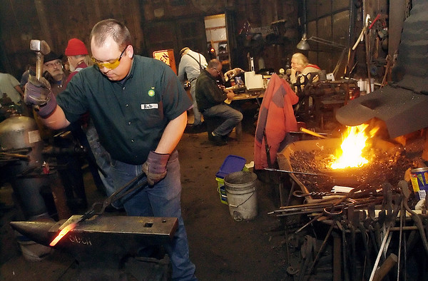 Record-Eagle/Garret Leiva<br /> Rob Hentschel, of Traverse City, strikes while the iron is hot on his tong project Saturday at the Folly at the Forge held at Black Rock Forge in Traverse City.