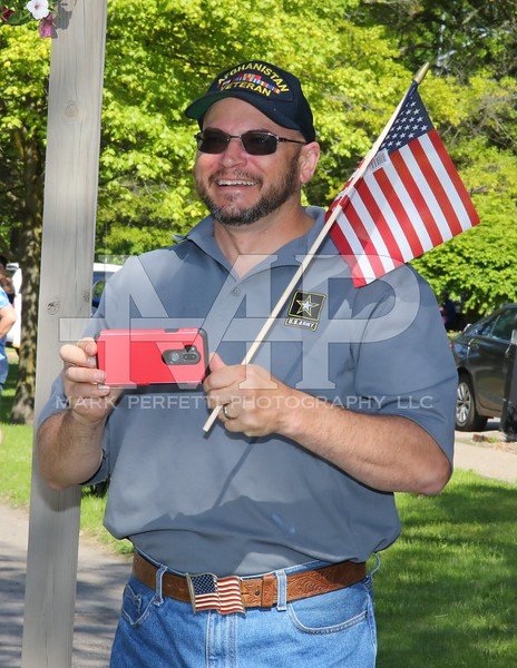 Veteran Carl Rice takes photos of his daughters as they pass by in the parade