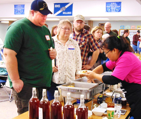 Debbie Blank | The Herald-Tribune Curing the Taste of Southeast Indiana, owner Mayasari Effendi (from right) of Mayasari Indonesian Grill, Greensburg, serves skewered chicken with peanut sauce to Mary Roller, Rushville, and Tony Schneider, Batesville.