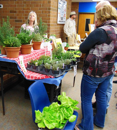 Debbie Blank | The Herald-Tribune        Vendor Beth Harnist (left), Adopt-A-Plant Garden Center, Harrison, Ohio, owner, answers questions about her greenhouse-grown herbs and hydroponic lettuce.