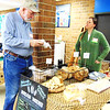 Debbie Blank | The Herald-Tribune<br /> John Miller (left) checks out bread baked by Michelle Kovach of Crackling Crust Microbakery, Cincinnati.