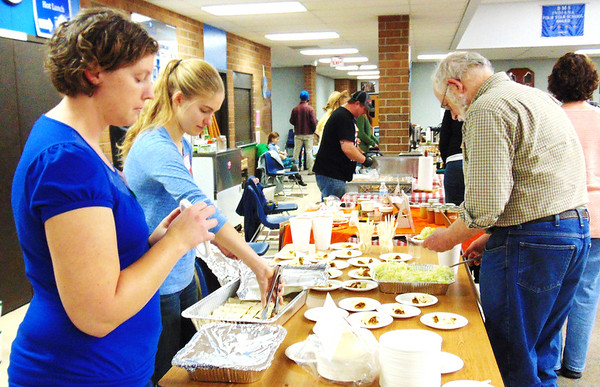 Debbie Blank | The Herald-Tribune<br /> Vendor Anne Meer (from left) and FGA board member Kristen Giesting serve beef enchiladas to Doug Ross, Milton, during the Taste of Southeast Indiana. Beef provided by Michaela Farm was turned into samples by The Toros.