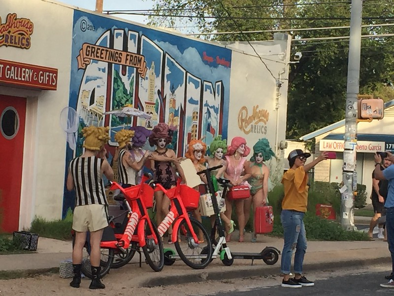 """We got back to the car, then had a nice Tex-Mex meal with margaritas before we headed back to the airport. We detoured to see the """"Greetings from Austin"""" mural and found this gathering of people all dressed up in crazy wigs and make up in front of the mural."""