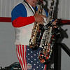 The band's saxman playing 2 saxaphones at once.