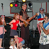 """A very lively group of little girls were dancing in front of the stage, so Johnny invited them to join the band on the stage. He dubbed them the """"Dee-lites"""" because they are little people helping Dee and the band."""