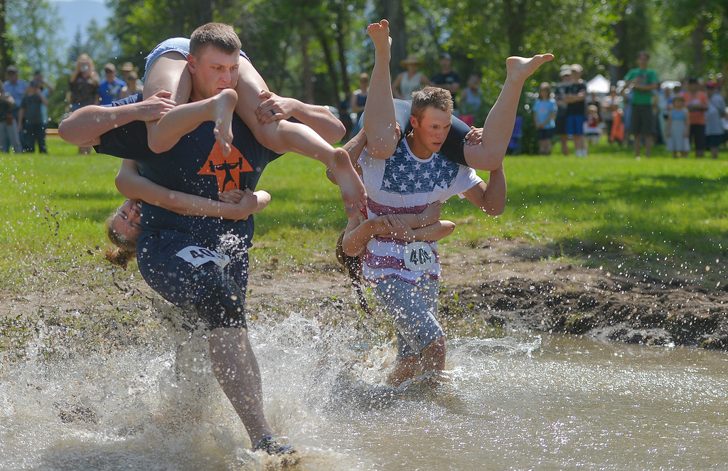 Justin Sheely | The Sheridan Press <br /> Brian Freed with Lillian Freed, left, and Mark Kopman with Shara Flores race through the water in the wife-carrying competition during the Independence Day celebrations Tuesday at Connor Battlefield State Historic Site in Ranchester.