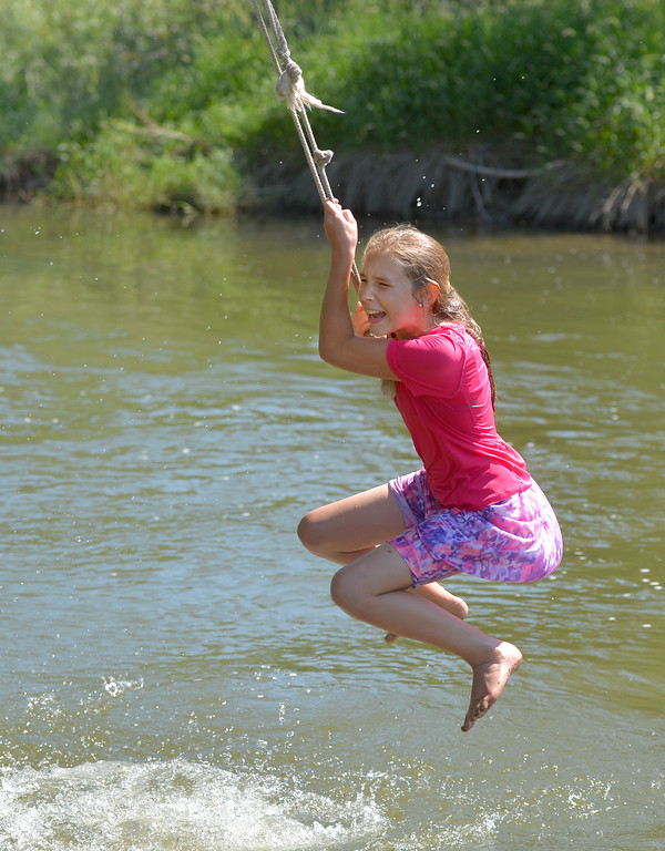 Justin Sheely | The Sheridan Press <br /> Twelve-year-old Elly Vollmer forgets to let go of the rope over the Tongue River during the Independence Day celebrations Tuesday at Connor Battlefield State Historic Site in Ranchester. The town of Ranchester hosted its annual celebration on the Fourth of July with live music from the Two Tracks, family games, food and other special events including the wife-carrying competition.