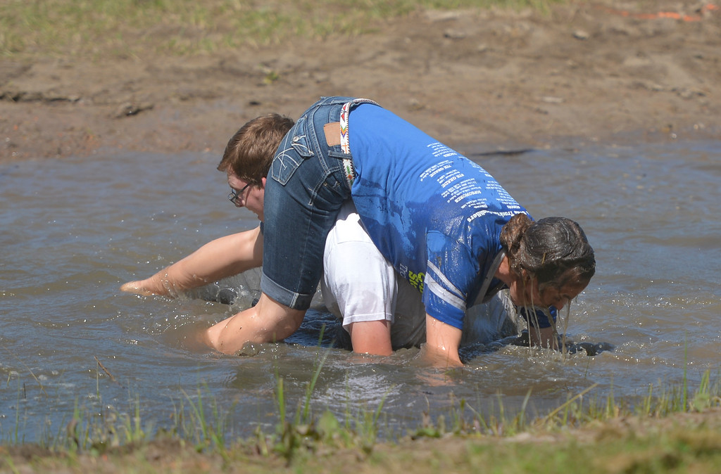 Justin Sheely | The Sheridan Press <br /> Brian Belus recovers from a fall in the water as he and Lela Belus compete in the wife-carrying competition during the Independence Day celebrations Tuesday at Connor Battlefield State Historic Site in Ranchester.