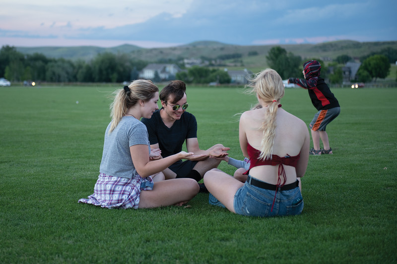 "Matthew Gaston | The Sheridan Press<br>From left, Sidney Wilson, Tucker Pimsner, Ameila Morten (blocked from view) and Amber Grutzmacher play a game of ""Down by the Banks"" before the fireworks display at the Big Horn Equestrian Center Saturday, July 6, 2019."