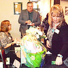 Debbie Blank | The Herald-Tribune<br /> Chamber Secretary Holly Murray (from left) of Stayin' Alive welcomes Joe Jester of Brookville IGA while executive director Rhonda Brown checks on a basket raffle item.