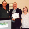 "Debbie Blank | The Herald-Tribune<br /> Board member Eugene Moster (from left) presented the Small Business/Organization Award to a business ""that makes a significant contribution or impact to the county"" because of integrity, goodwill, character and innovativeness – Third Place Event Center, owned by Mick and Jenny Wilz."