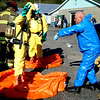 Debbie Blank | The Herald-Tribune<br /> Greater Cincinnati HAZMAT Analytical Response Unit member Bruce Ehas (from right), Forest Park, Ohio, teaches firefighters how to spray persons exposed to hazardous materials -- fellow members Jon Buesing, West Harrison, and Jordan Sonneville, Blue Ash, Ohio, to decontaminate them.