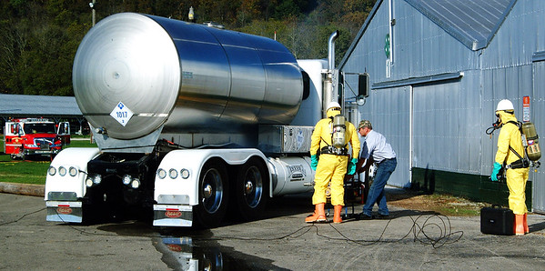 Debbie Blank | The Herald-Tribune<br /> Earlier a fog machine was used to simulate chlorine escaping from the punctured tank on the truck. The job of the Greater Cincinnati HAZMAT Analytical Response Unit (in yellow) is to verify the situation, relay what they found and suggest how to control the incident.