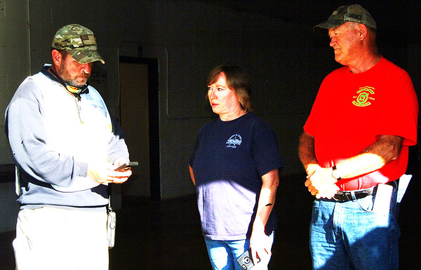 """Debbie Blank   The Herald-Tribune<br /> Indiana Department of Homeland Security District 9 coordinator Doug Cooke (from left) educates county Coroner Wanda """"Tink"""" Lee and Eagle Fire Co. volunteer Charlie Israel, Oldenburg, who was observing the exercise."""