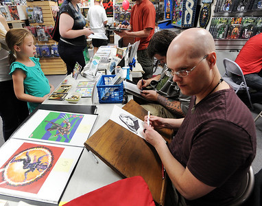 Comic artist, Scorpio Steel, right,  draws a character at the Time Warp event on Saturday. Time Warp Comics and Games in Boulder is one of thousands of comic book shops around the world celebrating the comic book art form on Saturday, May 5th. On Free Comic Book Day, over 3.3 million comic books will be given away by participating stores, introducing as many people as possible to the wonders of comic books! For a video and more photos of comic book day, go to www.dailycamera.com. Cliff Grassmick / May 5, 2012