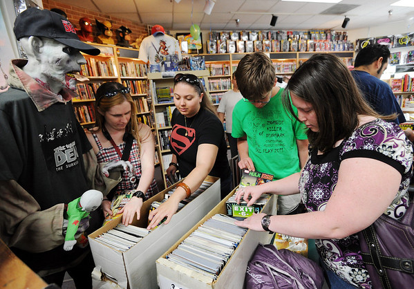 """Kira Berry, left, Laura Gomez, Ryan Earles, and Lili Armstrong, look through comics at Time Warp. The ghoul on the left refused to give his name.<br /> Time Warp Comics and Games in Boulder is one of thousands of comic book shops around the world celebrating the comic book art form on Saturday, May 5th. On Free Comic Book Day, over 3.3 million comic books will be given away by participating stores, introducing as many people as possible to the wonders of comic books!<br /> For a video and more photos of comic book day, go to  <a href=""""http://www.dailycamera.com"""">http://www.dailycamera.com</a>.<br /> Cliff Grassmick / May 5, 2012"""