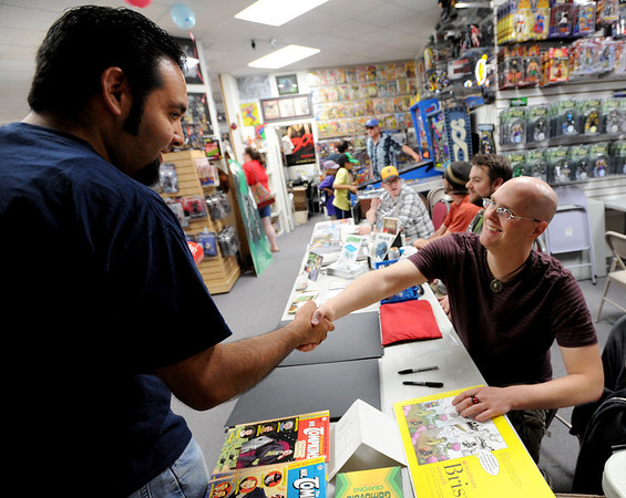 "Michael Hernandez, left, greets comic artist, Scorpio Steel, at the Time Warp event on Saturday.<br /> Time Warp Comics and Games in Boulder is one of thousands of comic book shops around the world celebrating the comic book art form on Saturday, May 5th. On Free Comic Book Day, over 3.3 million comic books will be given away by participating stores, introducing as many people as possible to the wonders of comic books!<br /> For a video and more photos of comic book day, go to  <a href=""http://www.dailycamera.com"">http://www.dailycamera.com</a>.<br /> Cliff Grassmick / May 5, 2012"