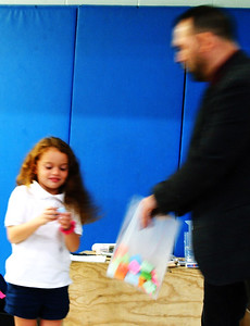 Pyanna Lynn, 6, Batesville, drew the name of a character from the magician's bag full of names. She kept it to herself while he cut up a piece of white paper.