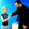 """Caroline Ramsey, 8, Batesville, holds a spoon that the magician proceeded to bend. """"This is why I never get invited to dinner,"""" he joked."""