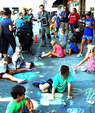 With encouragement from visiting artist David Zinn (center), Michigan, about 30 kids got creative with chalk on the downtown sidewalk as 30 adults watched during a Batesville Area Arts Council Arts in Education Evening Series program Sept. 13 from 4:30-6:30 p.m. on George Street sidewalks.