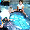 Two 7-year-olds, Wyatt Essick (left) and Allie Cox, use a smear technique for the background surrounding their chalk alien.