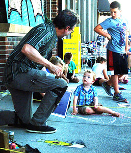 Illustrator and street chalk artist David Zinn pauses drawing one of his characters to interact with a toddler.