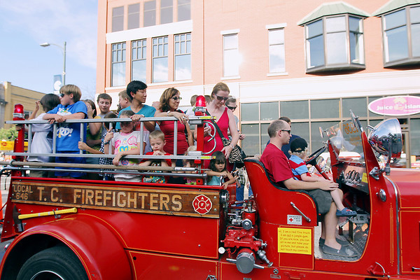 Record-Eagle/Keith King<br /> Rides are offered by Traverse City Firefighters on a 1936 American LaFrance fire truck Friday, July 22, 2011 during Friday Night Live.