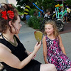 Record-Eagle/Keith King<br /> Bella Payeur, 4, of Dexter, smiles after looking into a mirror and seeing the flowers painted on the side of her face by Shawn Semelsberger, of Traverse City, Friday, July 22, 2011 during Friday Night Live.
