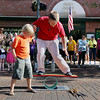 Record-Eagle/Keith King<br /> Bradley Salgat, 8, of Portage, assists Tom Bartholomew prior to Bartholomew's knife juggling act Friday, July 22, 2011 along Front Street during Friday Night Live.