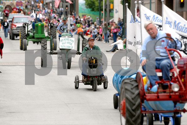 -Messenger photo by Hans Madsen<br /> <br /> Duane Johnson rides his three wheel creation in the Frontier Days Parade Saturday morning along Central Avenue in downtown Fort Dodge. The contraption is powered by a chainsaw engine.