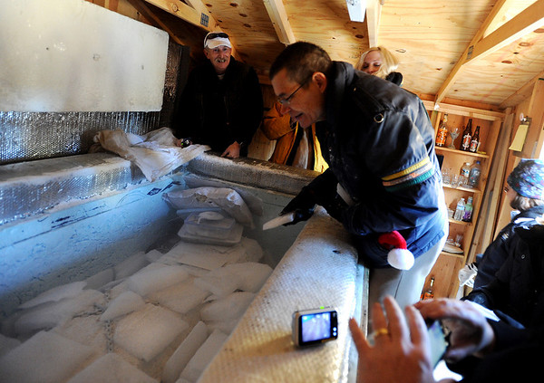 """Mike Perry, cenetr, had the honor of putting ice on the body of Bredo Morstoel. Bo Shaffer, top left, offers encouragement.<br /> As part of the 10th annual Frozen Dead Guys Days, a tours of Trygve Bauge's house outside Nederland  are given, including  at look at his frozen grandfather, Bredo Morstoel, who's body is in a Tuff Shed.<br /> For more photos and a video of the tour, go to  <a href=""""http://www.dailycamera.com"""">http://www.dailycamera.com</a>.<br /> Cliff Grassmick/ March 4, 2011"""