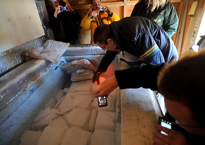 Mike Perry, center, had the honor of putting ice on the body of Bredo Morstoel.  As part of the 10th annual Frozen Dead Guys Days, a tour of Trygve Bauge's house outside Nederland  was given, including his frozen grandfather, who is in a Tuff Shed. Cliff Grassmick/ March 4, 2011