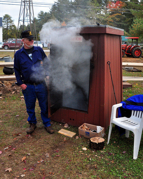 A member of the Fryeburg Fair staff tends a vintage meat smoker, in which a ham is being prepared. The 159th Maine blue ribbon classic runs thru October 11th, 2009.